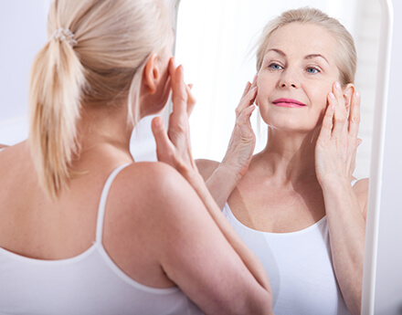 Woman Looking At Wrinkles in Mirror