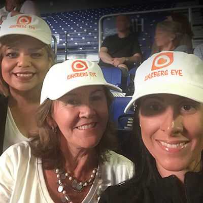 Three woman wearing white ginsberg hats and smiing