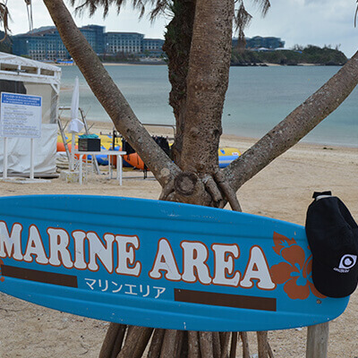 hat hung up on surfboard on beach