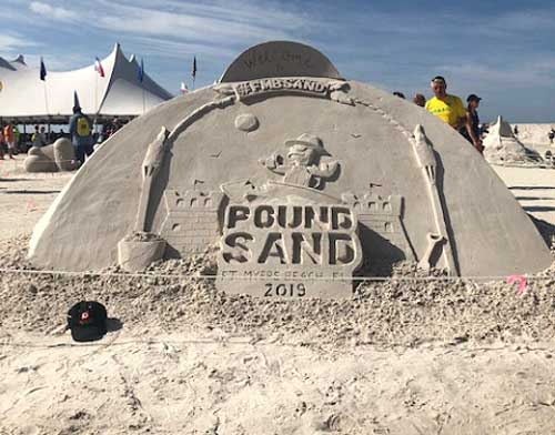 "Hat in front of sand castle that says ""pound sand"""