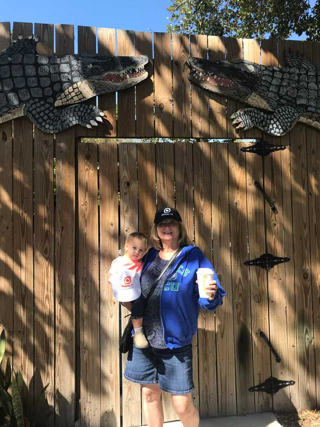 Woman holding baby in front of fake Alligators